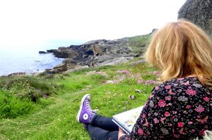 Photo of Jane painting watercolour sketch at Porth Hellick